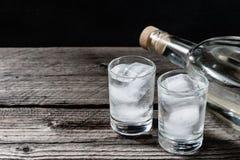 Vodca fria em vidros de tiro em um fundo preto Fotos de Stock Royalty Free