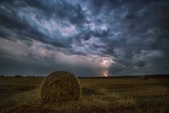 Vodden van hooi op het gebied en de bliksem nachtfoto, Royalty-vrije Stock Foto's