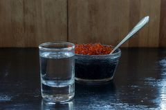 Vodka with black and red caviar on a black background royalty free stock photos