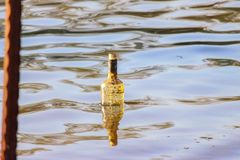 Vodka bottle floating in the river royalty free stock photos