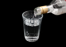 Vodka from the bottle is poured into a glass Stock Photo