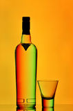 Vodka bottle and shot glass. Against orange gradient background Royalty Free Stock Photo