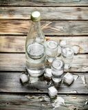 Vodka in a bottle and shot glasses with ice stock photos