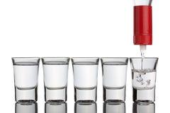 Vodka che versa nei vetri di colpo che si levano in piedi nella riga. Fotografia Stock