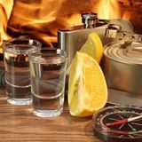 Vodka, compass, hip flask and food on the board at Fire Royalty Free Stock Photos