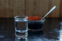 Vodka con el caviar negro y rojo en un fondo negro fotos de archivo libres de regalías