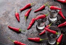 Vodka con pimientas de chile en la tabla oxidada del grunge Foto de archivo