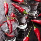 Vodka con pimientas de chile en la tabla oxidada del grunge Imagenes de archivo