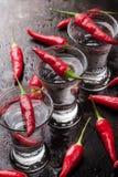 Vodka con pimientas de chile en la tabla oxidada del grunge Fotografía de archivo