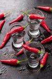 Vodka con pimientas de chile en la tabla oxidada del grunge Foto de archivo libre de regalías