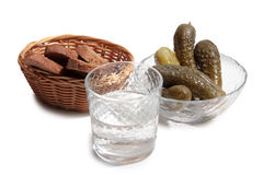 Vodka and cucumber. Vodka in glass and pickled cucumber on a white background royalty free stock image