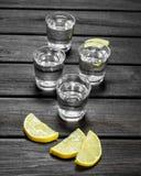 Vodka dans des tranches d'un verre à liqueur et de citron photos stock