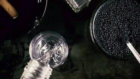Vodka de la cámara lenta en un vidrio y un caviar en un fondo negro almacen de video