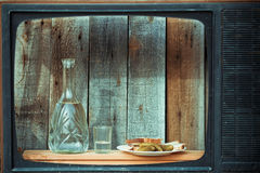Vodka decanter, glass and snack in the old TV. Image in the soft blue toning Royalty Free Stock Image