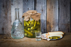 Vodka decanter, pickle and snack Stock Photos