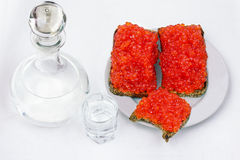 Vodka in a decanter, and sandwiches with red caviar Royalty Free Stock Photo