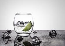 Vodka eller gin med limefrukt i ett ovalt exponeringsglas på en glansig grund med iskuber mot en vit tillbaka tänd bakgrund arkivfoto