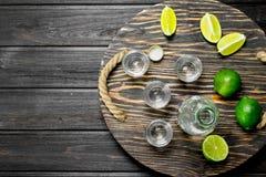 Vodka en un vaso de medida y una botella en la bandeja con la cal imágenes de archivo libres de regalías