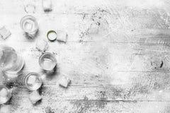 Vodka en una botella y cubos de hielo imagen de archivo libre de regalías