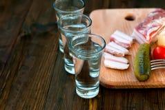 Vodka fredda in un vetro ed in un cetriolo su una tavola di legno Fotografia Stock