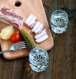 Vodka fredda in un vetro ed in un cetriolo su una tavola di legno Immagini Stock