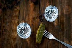 Vodka fredda in un vetro ed in un cetriolo su una tavola di legno Immagini Stock Libere da Diritti