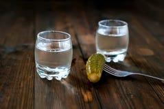 Vodka fredda in un vetro ed in un cetriolo su una tavola di legno Fotografie Stock Libere da Diritti