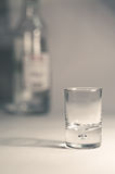 Vodka glass. And bottle in back Stock Images