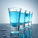 Vodka glass with ice on blue background. Vodka glass with ice on blue studio background Royalty Free Stock Photography