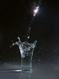 Vodka glass with splashes royalty free stock images