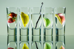 Vodka glasses with fuit. Shot glasses filled with vodka and fuit lined up in a row Stock Photos