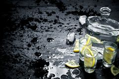 Vodka in glasses with lemon and ice. On the black chalkboard Royalty Free Stock Photography