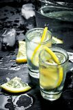 Vodka in glasses with lemon and ice. On the black chalkboard Stock Images
