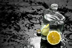 Vodka in glasses with lemon and ice. On the black chalkboard Stock Photos
