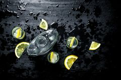 Vodka in glasses with lemon and ice. On the black chalkboard Stock Image