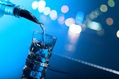 Vodka hälls från flaskan in i ett exponeringsglas arkivfoton