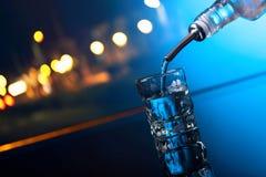 Vodka hälls från flaskan in i ett exponeringsglas royaltyfri fotografi