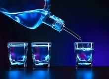 Vodka hälls in i ett exponeringsglas royaltyfria bilder