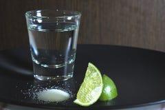 Vodka i ett exponeringsglas, alkohol, limefrukt som är salt arkivfoton