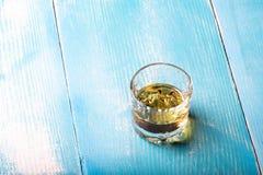 Vodka i ett exponeringsglas på tabellen royaltyfri fotografi