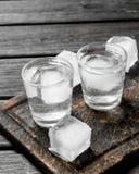 Vodka i ett skjutit exponeringsglas av is på skärbrädan royaltyfria bilder