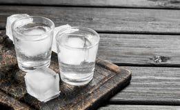 Vodka i ett skjutit exponeringsglas av is på skärbrädan fotografering för bildbyråer