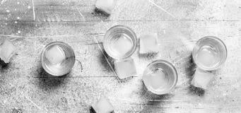Vodka i ett skjutit exponeringsglas och iskuber arkivbild