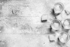 Vodka i ett skjutit exponeringsglas och iskuber fotografering för bildbyråer