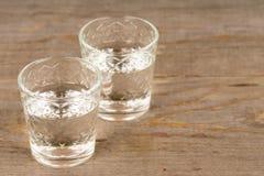 Vodka i sköt exponeringsglas på den lantliga trätabellen arkivbilder