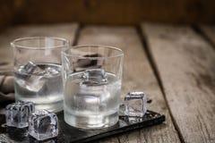 Vodka i skottexponeringsglas på lantlig wood bakgrund royaltyfria bilder