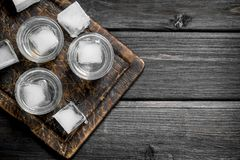 Vodka on the ice on the cutting Board. On black wooden background stock photo