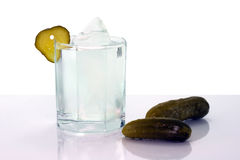 Vodka with ice in glass and salt cucumbers Stock Photography