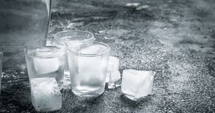 Vodka with ice in glasses. On a rustic background Stock Images