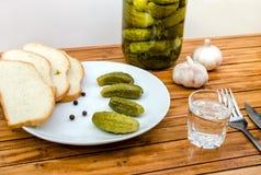 Vodka, inlagda gurkor, bröd och vitlök på en trätabell arkivfoton